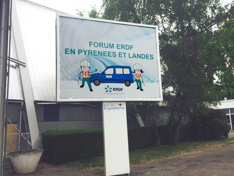 affiche de l'événement avec les mascottes devant le parc des expositions de Pau